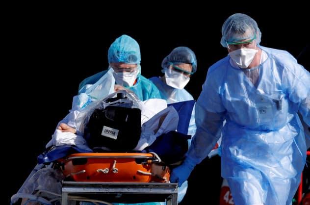 新型コロナに感染した患者を緊急搬送する救急隊員(24日、フランス)=ロイター