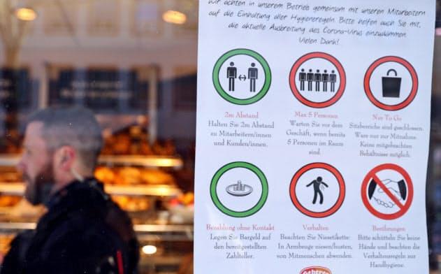 ドイツ西部ハーナウで、商店が営業許可を得ているか確認する警官=ロイター