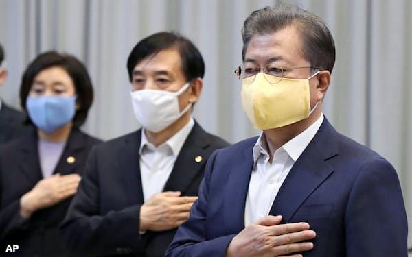 文在寅・韓国大統領(右)は新型コロナウイルス対策と経済対策を両立させようとしているが…(3月、ソウル)=AP