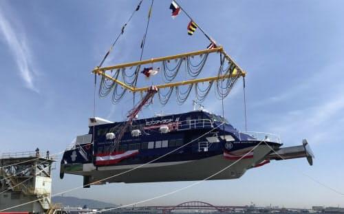 25年ぶりに新造した超高速旅客船「ジェットフォイル」はクレーンにつり下げられて海に着水した(26日、神戸市の川重神戸工場)