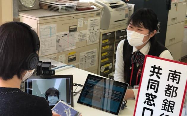 利用者はタブレットを使って行員(左下)とテレビ通話する(26日、奈良県黒滝村)