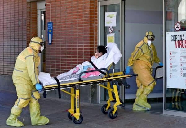 26日、患者を病院に運ぶ救急隊員(マドリード近郊)=ロイター