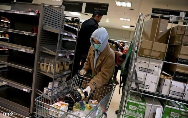 ロンドンのスーパーマーケットでマスクを付けてパスタを購入する人=ロイター