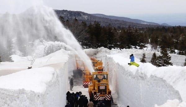 八甲田・十和田ゴールドラインで雪を吹き上げる除雪車(27日、青森県の傘松峠)=共同