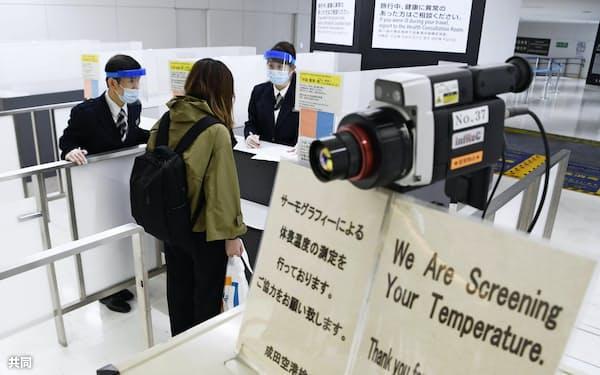 検疫官から質問を受ける米国便で到着した乗客(26日、成田空港)=共同