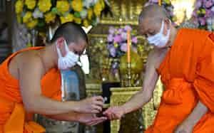 日本企業もタイ版GDPRへの対応を迫られる(手を消毒する僧侶たち、タイ・バンコク)=ロイター