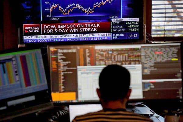 臨時オフィスで働くニューヨーク証券取引所のフロアトレーダー(26日、ニューヨーク)=ロイター