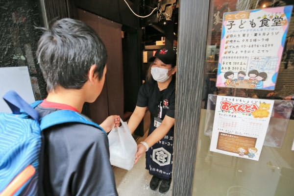 外出自粛要請の週末も「支援が必要」と、店内飲食を避けてお弁当を手渡す子ども食堂のスタッフ(28日午前、東京都豊島区)