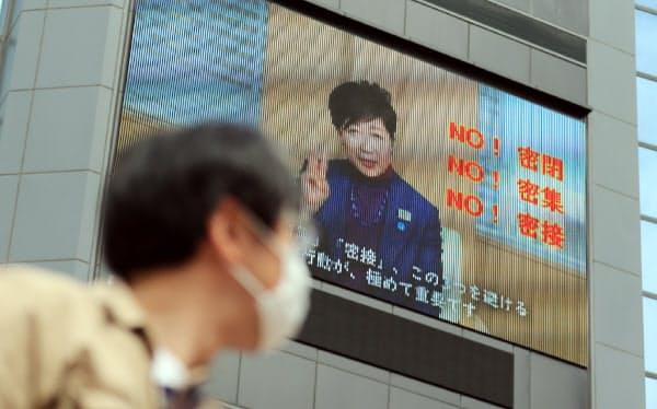 新型コロナウイルス対策を訴える小池都知事を映し出す街頭の大型モニター(28日、東京都渋谷区)