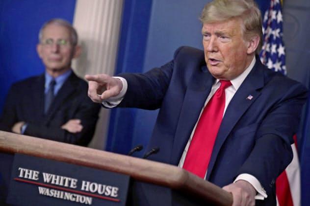 ホワイトハウスで記者会見するトランプ米大統領(右)と国立アレルギー・感染症研究所のファウチ所長=ロイター