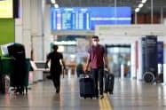 マスクをして空港を歩く旅行者(25日、ブラジリア)