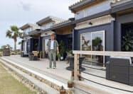 ログハウス型仮設住宅の解体資材で建設された複合商業施設と福山大洋さん(26日、鹿児島県・沖永良部島)=共同