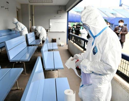 ナゴヤ球場の一塁側ベンチ内を消毒する防護服の作業員(30日午前、名古屋市)=共同