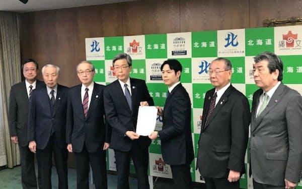 北海道の鈴木直道知事(右から3人目)に経済対策を求める北海道の経済8団体(30日、北海道庁)