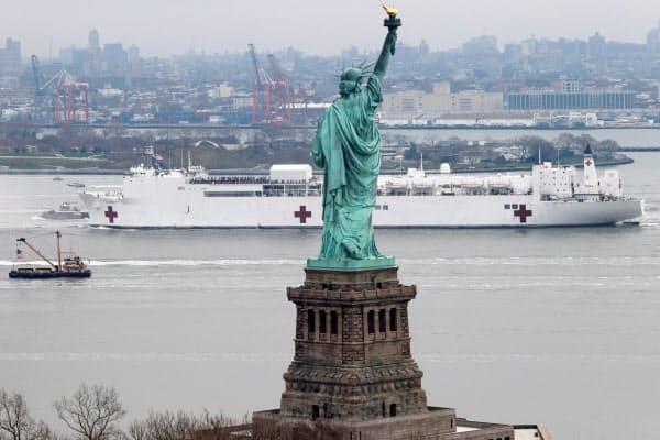 自由の女神像を通過する病院船「コンフォート」(30日、ニューヨーク)=ロイター