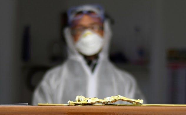 防護服を着て棺の横に立つ葬儀会社関係者(30日、イタリア南部のチステルニーノ)=ロイター