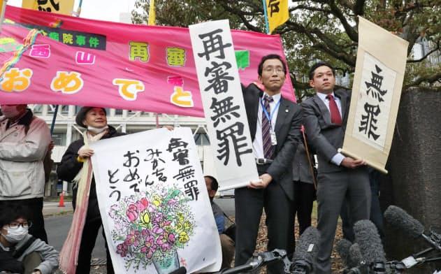 西山さんの再審無罪判決を知らせる垂れ幕を掲げる弁護士(31日午前、大津市)