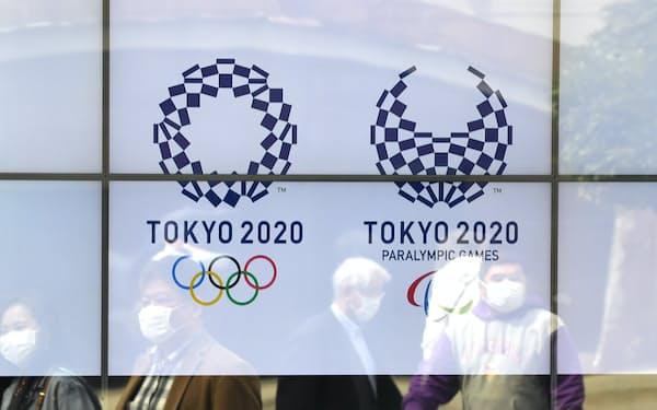 街頭のモニターに表示された東京五輪・パラリンピックのロゴマーク(3月、東京都港区)