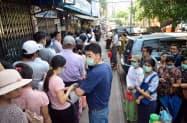 新型コロナウイルスの感染拡大に備え、市販薬を買うために薬局に並ぶ人々(24日、ヤンゴン)