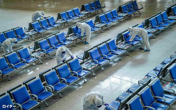 新型コロナは中国の交通を寸断した(3月、武漢駅を消毒する人たち)=ロイター