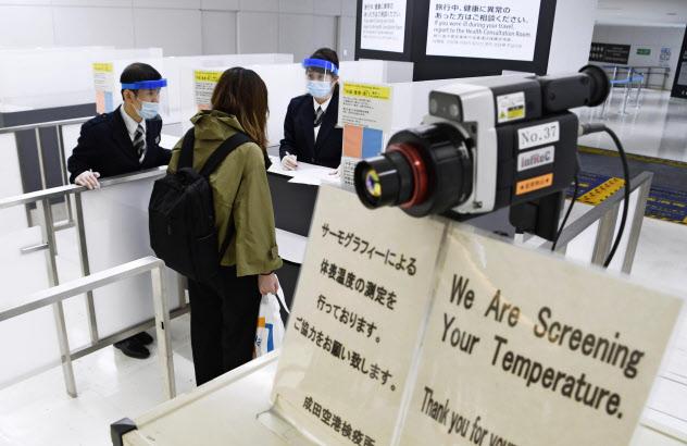 検疫官から質問を受ける米国便で到着した乗客=26日午後、成田空港