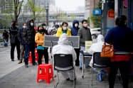 銀行の入り口で順番を待つ市民(3月31日、中国湖北省武漢市)=ロイター