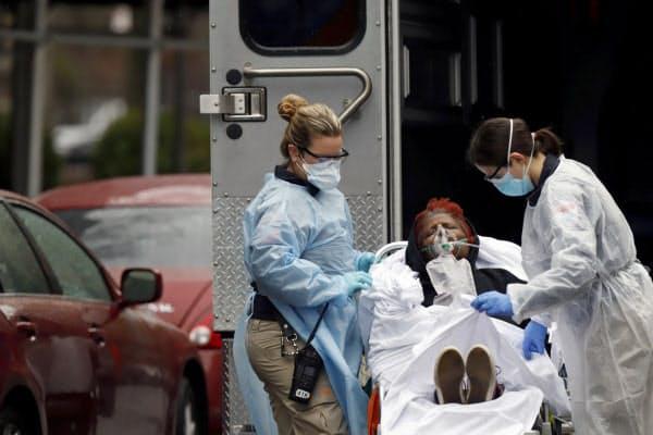 新型コロナ患者を救急車に乗せる医療関係者(ニューヨーク市)=ロイター