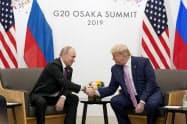 プーチン氏(右)はトランプ氏との電話協議で医療機器などの支援を提案した(2019年6月、大阪で開かれた米ロ首脳会談)=ロイター