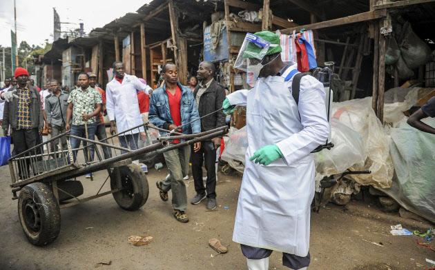 ケニアの首都ナイロビの屋外市場で、手押し車に消毒剤をかける保健省当局者=AP