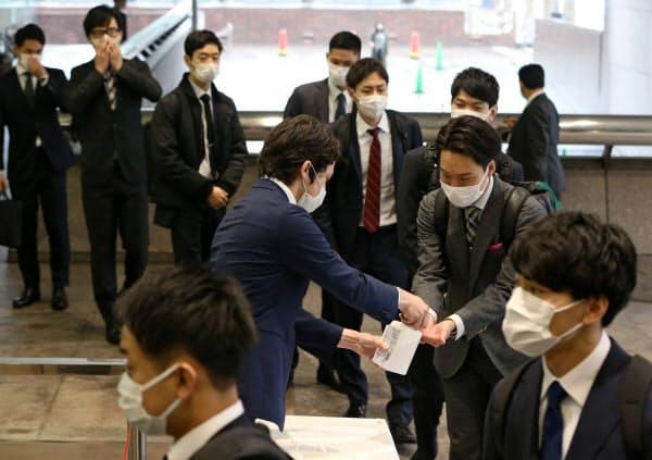 初出社し、入り口で手指の消毒をする伊藤忠商事の新入社員(1日、東京都港区)