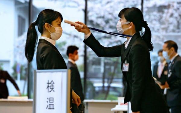 新型コロナ対策で入行式前に検温する西日本シティ銀行の新入行員(左)(1日、福岡市中央区)