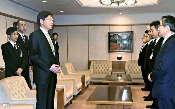 神戸市役所で久元喜造市長(手前左)と面会する関西電力の森本孝社長(同右)=1日午前、共同
