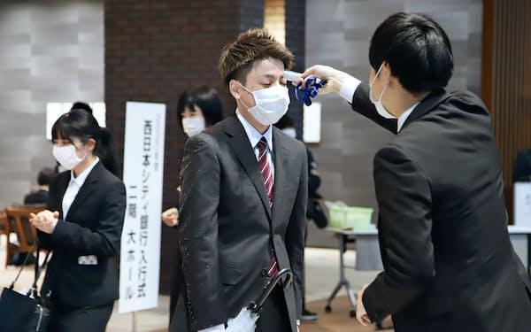新型コロナウイルス対策で、入行式前に検温を受ける西日本シティ銀行の新入行員(右から2人目)=1日、福岡市