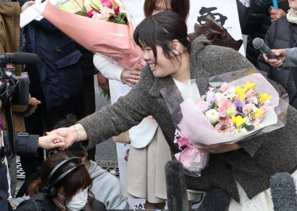 無罪判決を受け笑顔で支援者と握手する西山さん(3月31日午後、大津市)
