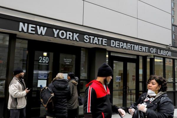 新型コロナの影響で閉まっているニューヨーク州労働局の事務所に集まる人々=ロイター