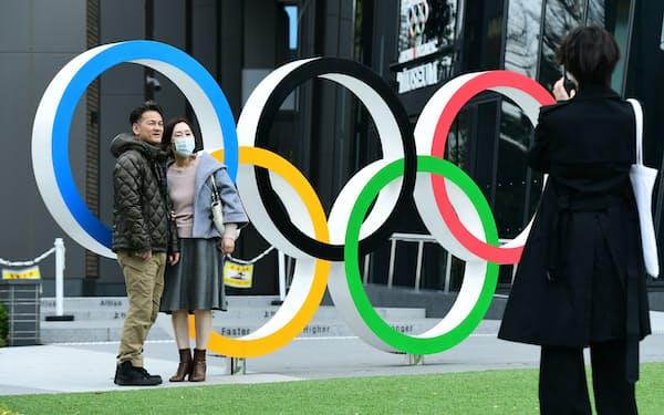 国立競技場近くに設けられた五輪マークのモニュメントの前で記念撮影する人たち(東京都新宿区)