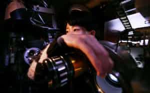 映写機にフィルムを装着し、スクリーンを見ながらピントを合わせる見習いの寺本さん=目良友樹撮影