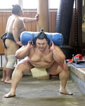 砂袋を担いですり足に励む朝乃山(3日、東京都墨田区の高砂部屋)=共同