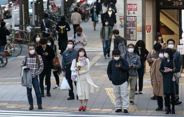 マスクを付けて信号を待つ人たち(4日、東京都新宿区)