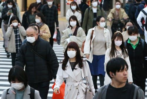 マスクを着けて歩く人たち(4日、東京都新宿区)