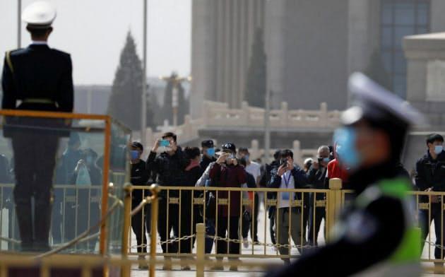 北京の天安門広場でスマートフォンを使う人々にも監視の目が向けられる=ロイター