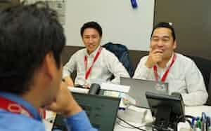 マネーコミュニケーションズを実質的に立ち上げた田中営業部長(右)は社員と膝詰めでビジネスプランを練り上げている