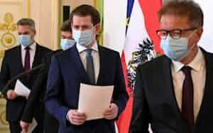 対コロナ規制の緩和を発表するマスク姿のクルツ首相(中)=ロイター