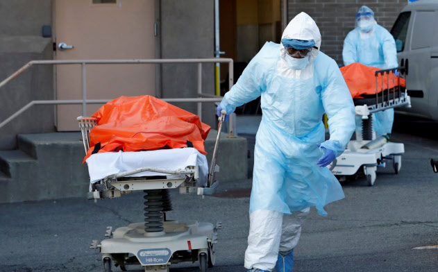 新型コロナ患者の遺体を運ぶ医療スタッフ=ロイター