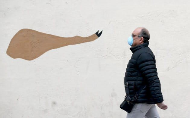 スペイン名物のイベリコ豚のハムのイラストが壁に描かれたマドリード市内をマスクをして歩く男性=ロイター