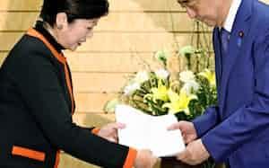 安倍首相(右)に新型コロナウイルス対策の要望書を渡す小池都知事(3月26日、首相官邸)