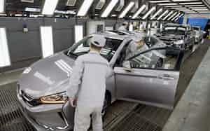 再開した自動車工場で働く労働者ら(3月、中国・武漢)=新華社・共同