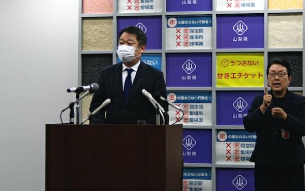 緊急事態宣言を受けて記者会見する山梨県の長崎幸太郎知事(左)(7日、甲府市内)