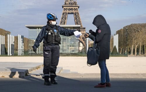 パリのエッフェル塔周辺で通行人を検問するマスク姿の警官=AP