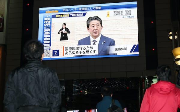 緊急事態宣言についての安倍首相の会見を放映する街頭ビジョン(7日、東京都新宿区)